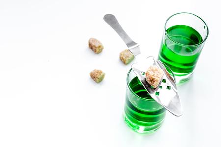 Foto de Traditions of drinking absinthe. Special spoon and sugar cubes near shots on white background top view copy space - Imagen libre de derechos