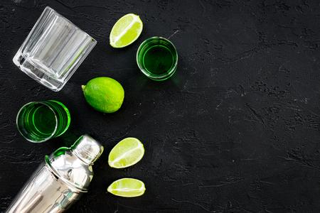 Foto de Make cocktail with absinthe. Shaker, shots, lime slices on black background top view space for text - Imagen libre de derechos