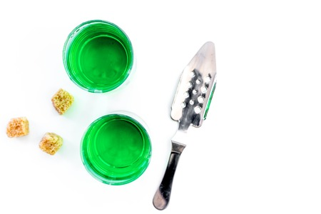 Foto de Traditions of drinking absinthe. Special spoon and sugar cubes near shots on white background top view. - Imagen libre de derechos
