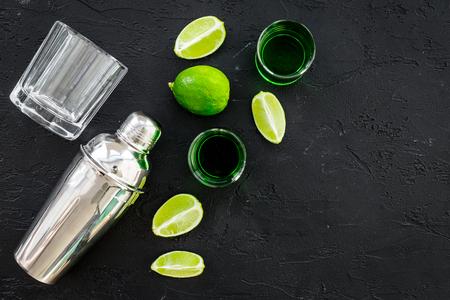 Foto de Make cocktail with absinthe. Shaker, shots, lime slices on black background top view. - Imagen libre de derechos