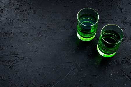 Foto de Absinthe shots on black background top view. - Imagen libre de derechos