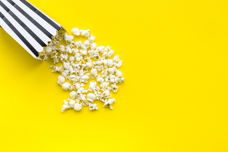 Foto de Popcorn in paper bag scattered on yellow background top view copy space - Imagen libre de derechos