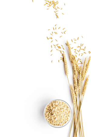 Photo for Cereals concept. Oatmeal in bowl near sprigs of wheat on white background top view copy space - Royalty Free Image
