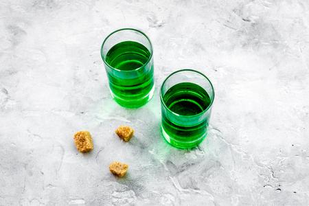 Foto de Absinthe shots near sugar cubes on grey background top view. - Imagen libre de derechos