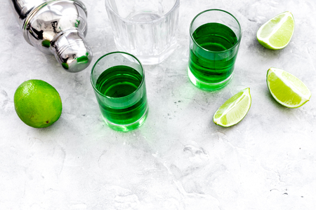 Foto de Make cocktail with absinthe. Shaker, shots, lime slices on grey background top view. - Imagen libre de derechos