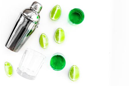 Foto de Make cocktail with absinthe. Shaker, shots, lime slices on white background top view, - Imagen libre de derechos