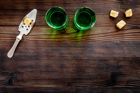 Foto de Traditions of drinking absinthe. Special spoon and sugar cubes near shots on dark wooden background top view. - Imagen libre de derechos
