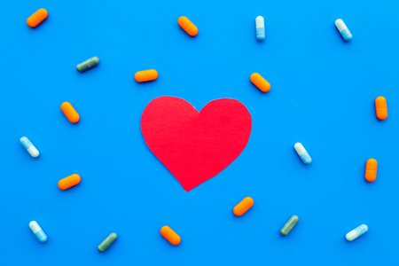 Foto de Vitamins of drugs for heart. Color pills near heart sign on blue background top view. - Imagen libre de derechos