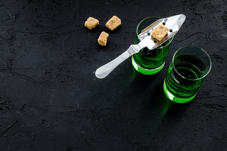 Foto de Traditions of drinking absinthe. Special spoon and sugar cubes near shots on black background top view. - Imagen libre de derechos