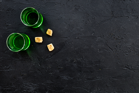 Foto de Absinthe shots near sugar cubes on black background top view. - Imagen libre de derechos