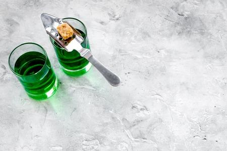 Foto de Traditions of drinking absinthe. Special spoon and sugar cubes near shots on grey background top view. - Imagen libre de derechos