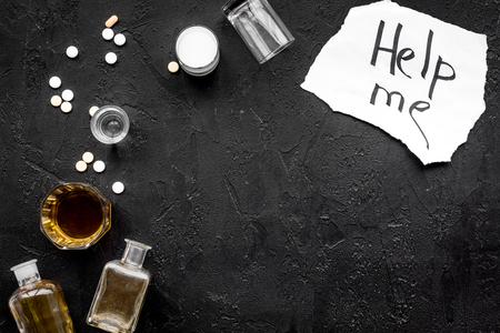 Foto de Treat alcohol dependence. Words Help me near glasses, bottles and pills on black background top view. - Imagen libre de derechos