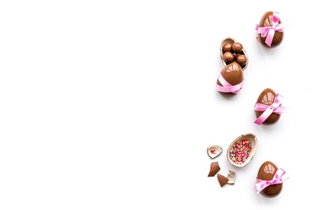 Photo for Sweets for Easter table. Chocolate eggs near cookies in shape of Easter bunny on white background top view copy space - Royalty Free Image