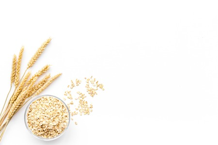 Photo pour Cereals concept. Oatmeal in bowl near sprigs of wheat on white background top view. - image libre de droit