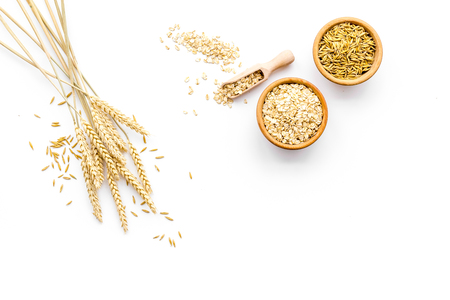Photo for Oatmeal and oat in bowls near sprigs of wheat on white background top view copy space - Royalty Free Image