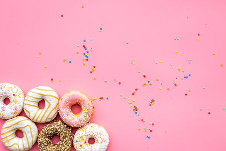 Photo for Donuts decorated icing and sprinkles on pink background top view copy space pattern - Royalty Free Image