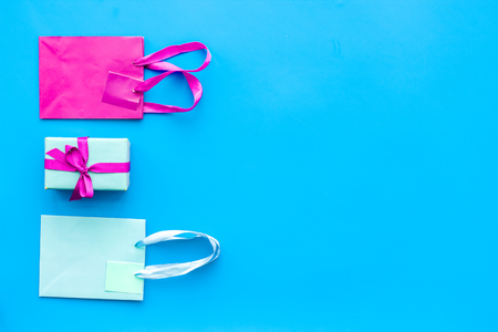 Photo for Gift box and colorful paper bag on blue background top view mock-up. - Royalty Free Image