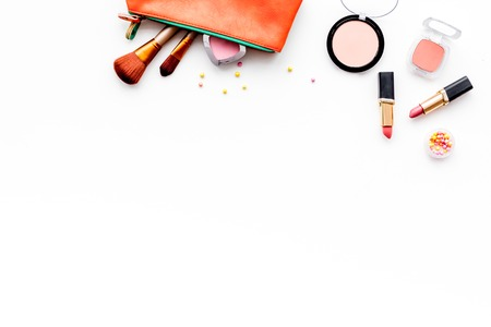 Photo pour Decorative cosmetics background. Eyeshadow, rouge, brushes, lipstick in cosmetic bag on white top view copy space - image libre de droit