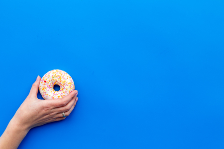 Photo for Sweet tasty snack. Glazed donut on blue table background top view copy space - Royalty Free Image