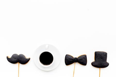 Photo pour Fathers Day celebration concept. Monochrome. Cookies in shape of moustache, hat, bow tie near coffee on white background top view copy space - image libre de droit