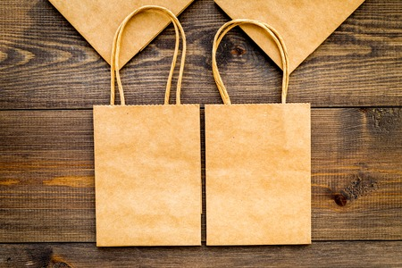 Photo pour Brown kraft paper bag for shopping on wooden background top view mockup - image libre de droit
