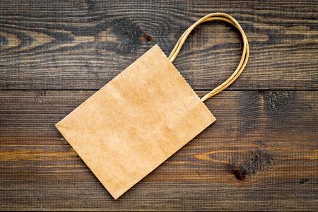 Photo pour Brown kraft paper bag for shopping on wooden background top view copy space - image libre de droit