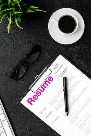 Photo for Review resumes of applicants. Resume on black work desk with coffee, glasses, keyboard top view. - Royalty Free Image