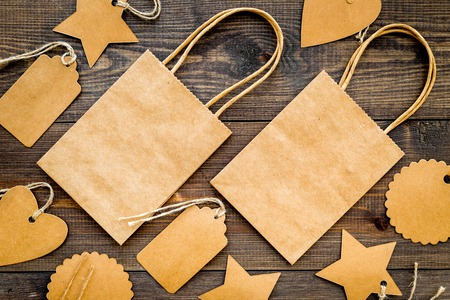 Photo pour Brown kraft paper bag for shopping near price tags on wooden background top view mockup - image libre de droit