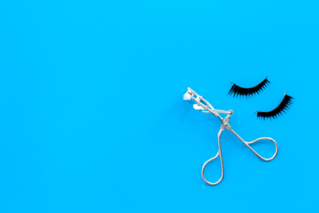 Photo pour Curled and thick eyelashes. False eyelashes and eyelash curler on blue background top view. - image libre de droit