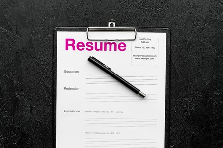 Photo for Empoyment concept. Resume on pad near pen and glasses on black background top view. - Royalty Free Image