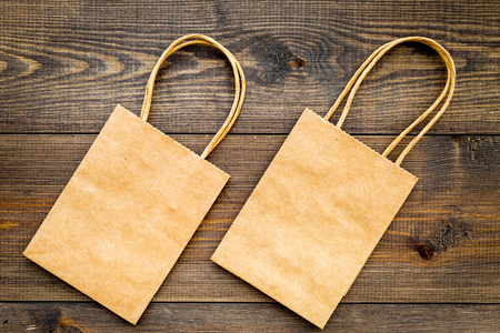 Photo pour Brown kraft paper bag for shopping on wooden background top view. - image libre de droit