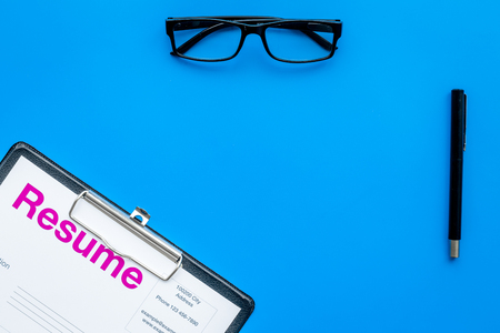 Photo for Looking for work concept. Resume on pad near pen and glasses on blue background top view space for text - Royalty Free Image