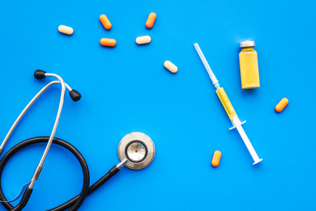 Foto de Medical examination and treatment concept. Stethoscope, syringe, pills on blue background top view - Imagen libre de derechos