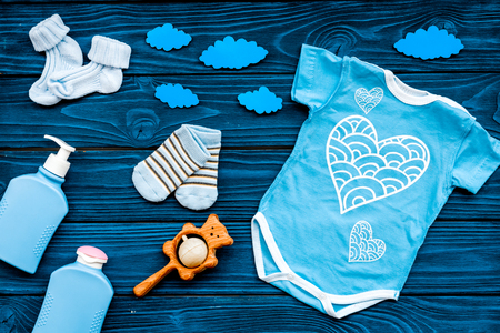 Photo pour Newborn baby's sleep concept. To put the child to bed. Baby bodysuit near clouds on blue wooden background top view. - image libre de droit