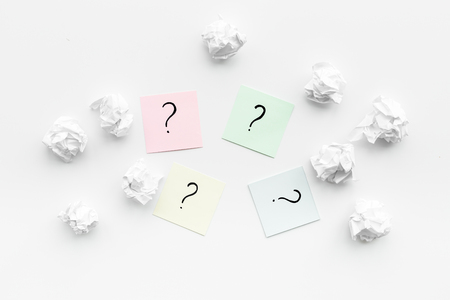 Foto de FAQ concept. Question mark on sticky notes near crumpled paper on white background top view - Imagen libre de derechos