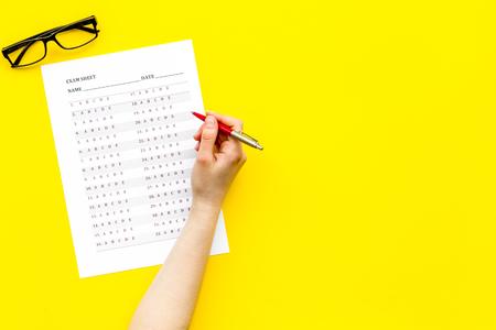 Foto de Take the exam, write the exam. Hand with pen near exam paper on yellow background top view copy space - Imagen libre de derechos