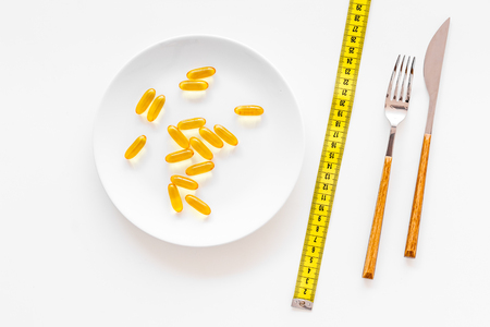 Photo pour Dietary supplement for well-being. Fish oil or omega-3 capsules on plate near measuring tape on white background top view. - image libre de droit