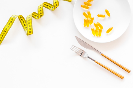 Photo for Dietary supplement for well-being. Fish oil or omega-3 capsules on plate near measuring tape on white background top view copy space - Royalty Free Image