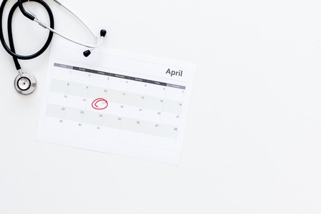 Foto de Planning medical examination concept. Regular medical examinations. Calendar with date circled and stethoscope on white background top view copy space - Imagen libre de derechos