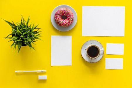 Photo pour Come up with brand identity. Blank stationery for branding near coffee and donut on yellow background top view mockup pattern. - image libre de droit