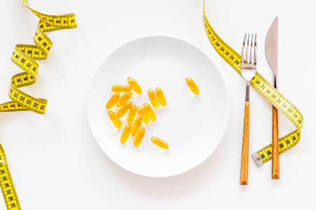 Photo pour Dietary supplement for well-being. Fish oil or omega-3 capsules on plate near measuring tape on white background top view - image libre de droit