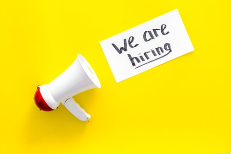 Photo for Job recruiting advertisement. We are hiring lettering near megaphone on yellow background top view copy space - Royalty Free Image