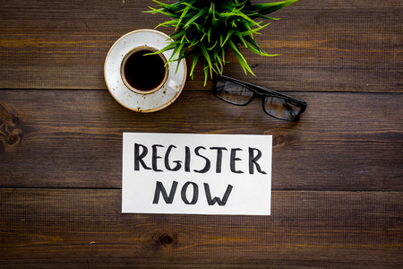 Photo for Membership concept. Template for registration. Register now hand lettering icon on word desk with glasses, coffee, plant on dark wooden background top view space for text - Royalty Free Image