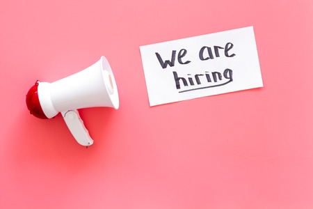Photo for Job recruiting advertisement. We are hiring lettering near megaphone on pink background top view copy space - Royalty Free Image