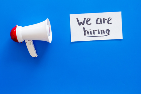 Photo for Job recruiting advertisement. We are hiring lettering near megaphone on blue background top view copy space - Royalty Free Image