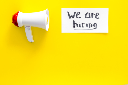 Photo pour Job recruiting advertisement. We are hiring lettering near megaphone on yellow background top view copy space - image libre de droit