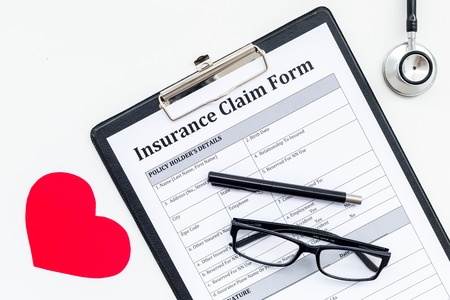 Photo pour Health insurance claim form for fill out. Empty form near heart sign and stethoscope on white background top view. - image libre de droit