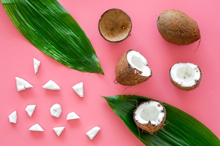 Photo pour Coconut background. Whole and cut coconuts, pulp and palm leaves on pink background top view - image libre de droit