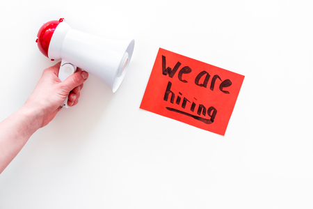 Photo for Job recruiting advertisement. We are hiring lettering near megaphone on white background top view copy space - Royalty Free Image