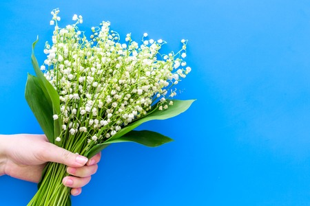Photo pour Give a bouquet of delicate lily of the valley flowers. Hand hold bunch of flowers on pastel blue background top view. - image libre de droit